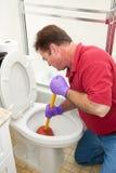 Uomo che utilizza tuffatore nella toilette fotografia stock libera da diritti