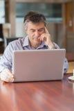 Uomo che utilizza un computer portatile in una caffetteria ed in un pensiero Fotografia Stock Libera da Diritti