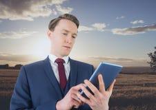 Uomo che utilizza una compressa digitale nella campagna fotografie stock