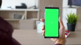 Uomo che utilizza uno smartphone moderno con il modello verde di intensità dello schermo nel suo salone archivi video