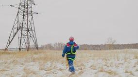 Uomo che va alla torre elettrica sulla stazione di energia al campo di inverno video d archivio