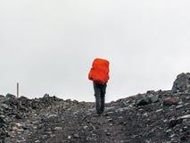 Uomo che va su collina con lo zaino pesante enorme fotografie stock