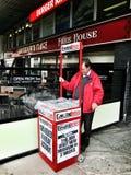 Uomo che vende i giornali a Edimburgo, Scozia Immagine Stock