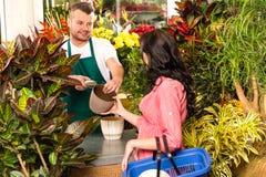 Uomo che vende il negozio di fiore del cliente della donna del vaso Fotografie Stock