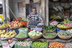 Uomo che vende le verdure nel mercato di strada a città santa Pushkar, Ragiastan, India fotografia stock