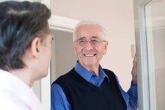 Uomo che verifica il vicino maschio anziano Fotografia Stock