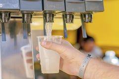 Uomo che versa bevanda fresca nella barra di self service immagine stock