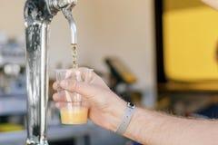 Uomo che versa birra fresca nella barra di self service - con tutto il distintivo incluso fotografia stock