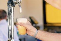 Uomo che versa birra fresca nella barra di self service - con tutto il distintivo incluso immagini stock libere da diritti