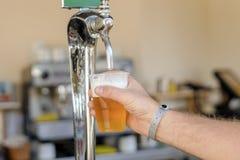 Uomo che versa birra fresca nella barra di self service - con tutto il distintivo incluso immagine stock