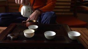 Uomo che versa il tè di Puer in teiera alla cerimonia di tè del cinese tradizionale Insieme di attrezzatura per tè bevente archivi video