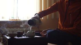 Uomo che versa il tè di Puer in teiera alla cerimonia di tè del cinese tradizionale Insieme di attrezzatura per tè bevente video d archivio