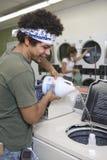 Uomo che versa soluzione liquida in lavatrice fotografia stock libera da diritti