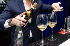 Uomo che versa vino rosso in un vetro immagine stock libera da diritti