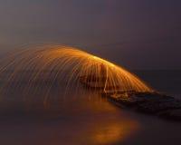 Uomo che volteggia i fuochi d'artificio sulla linea costiera Fotografie Stock Libere da Diritti