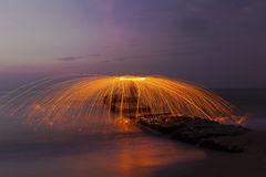 Uomo che volteggia i fuochi d'artificio sulla linea costiera Fotografia Stock Libera da Diritti