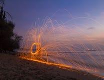Uomo che volteggia i fuochi d'artificio sulla spiaggia Fotografia Stock