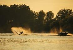 Uomo che wakeboarding sul lago dietro la barca Fotografia Stock