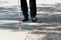 Uomo cieco con il bastone bianco sulla via immagini stock