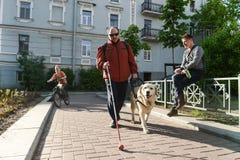 Uomo cieco e cane guida immagine stock