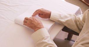 Uomo cieco senior che legge un libro di Braille stock footage