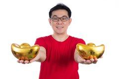Uomo cinese asiatico felice che porta camicia rossa che tiene lingotto Immagini Stock