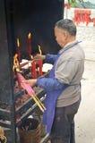 Uomo cinese che accende le candele in tempio Immagini Stock Libere da Diritti