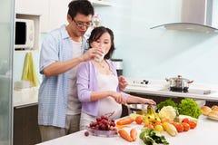 Uomo cinese che dà latte alla sua moglie incinta fotografia stock