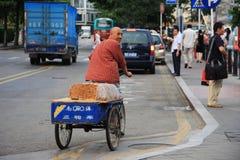 Uomo cinese che guida una bici che vende torta tradizionale Immagini Stock