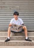 Uomo cinese che legge un giornale che si siede su una piccola scala, Pechino, Cina Immagine Stock