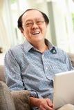 Uomo cinese maggiore che per mezzo del computer portatile mentre distendendosi Fotografie Stock