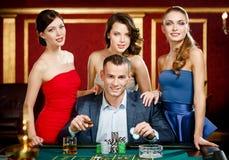 Uomo circondato dalle roulette dei giochi delle signore Immagini Stock