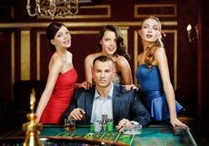 Uomo circondato dalle roulette graziose dei giochi delle ragazze Fotografia Stock