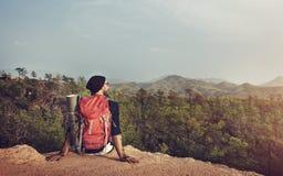 Uomo Cliff Backpacker Concept solo di seduta fotografia stock