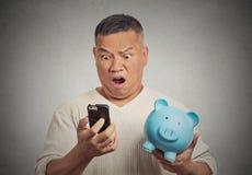 Uomo colpito che esamina il suo porcellino salvadanaio della tenuta dello Smart Phone Immagini Stock Libere da Diritti