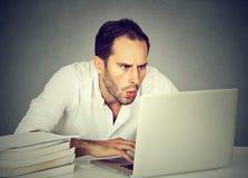 Uomo colpito di affari che si siede davanti al computer che esamina schermo Immagine Stock