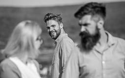 Uomo con aggressivo geloso della barba perché amica interessata a passante bello Concetto geloso Sorridere del passante fotografie stock