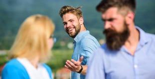 Uomo con aggressivo geloso della barba perché amica interessata a passante bello Marito che guarda rigorosamente la sua moglie fotografie stock libere da diritti