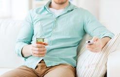 Uomo con birra e telecomando a casa Fotografia Stock