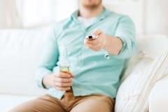Uomo con birra e telecomando a casa Fotografia Stock Libera da Diritti