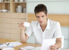 Uomo con caffè e lavorare alle finanze fotografia stock libera da diritti