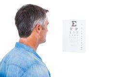 Uomo con capelli grigi che effettuano una prova dell'occhio Fotografia Stock