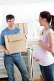Uomo con cartone che esamina la sua moglie incinta fotografia stock libera da diritti