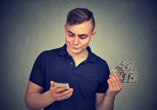 Uomo con contanti facendo uso dello smartphone fotografie stock libere da diritti