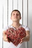 Uomo con cuore di legno fatto a mano che si siede vicino alla parete Fotografia Stock