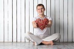 Uomo con cuore fatto a mano che si siede vicino alla parete Fotografia Stock
