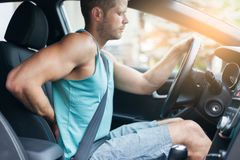 Uomo con dolore alla schiena dopo un azionamento lungo in automobile immagini stock