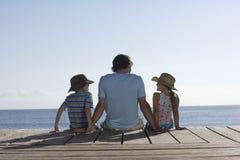 Uomo con due bambini che si siedono sul molo fotografie stock