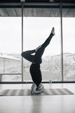 Uomo con esperienza di yoga che fa le varie pose all'interno, vista panoramica della città al fondo Immagine Stock