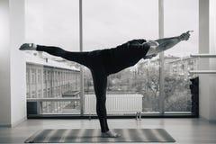Uomo con esperienza di yoga che fa le varie pose all'interno, vista panoramica della città al fondo Fotografia Stock